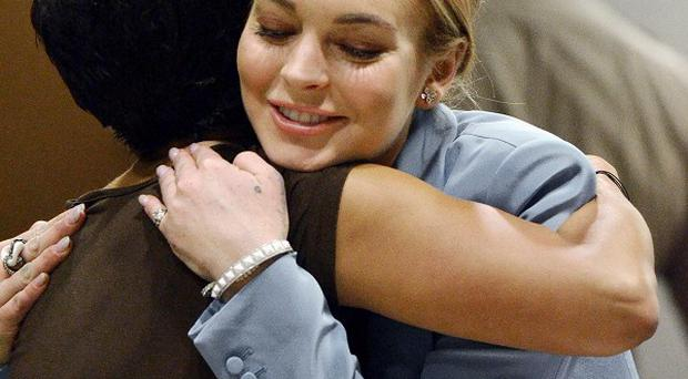 Lindsay Lohan embraces her lawyer after her probation order was lifted at Los Angeles Superior Court