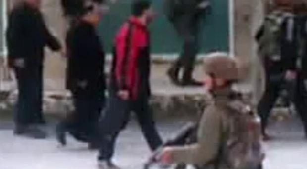 This image made from amateur video purports to show civilians moving with Syrian troops in Idlib, Syria (Shaam News Network)