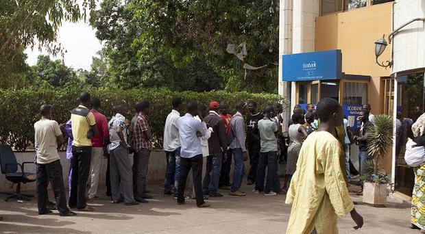 People stand in line outside a bank in Bamako, Mali (AP)