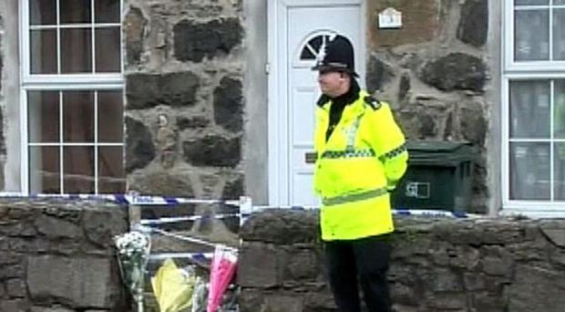 A police officer guards a house in Porthmadog, Gwynedd, after a man was arrested on suspicion of murdering a woman and her young son