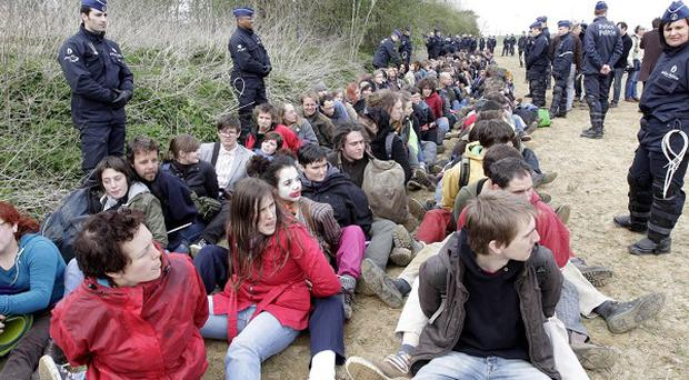 Activists are detained by police in a field outside Nato's headquarters in Brussels (AP)