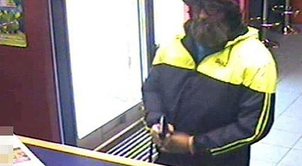 Martin Reilly wearing a disguise while committing armed robbery at William Hill in Hove