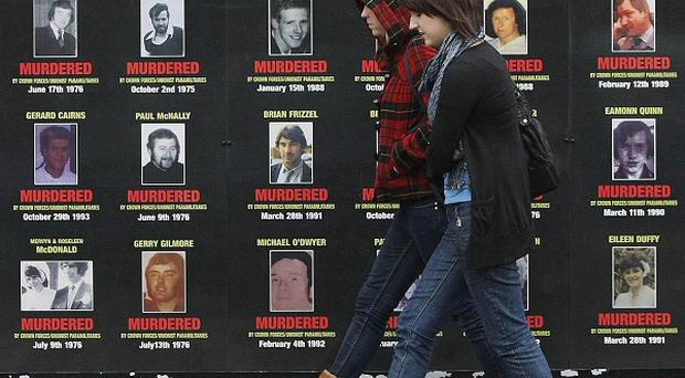 Two women walk past mural depicting victims of the Troubles in west Belfast