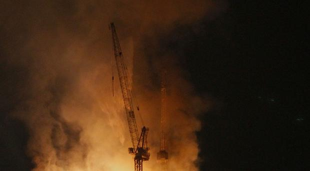 A firefighting helicopter drops water to extinguish a fire atop an under-construction skyscraper in Moscow (AP)
