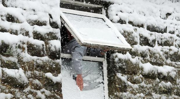 A man clears snow off his windows in Corbridge, Northumberland