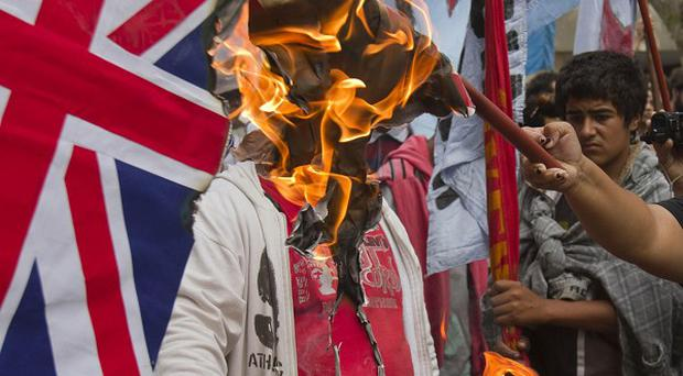 A demonstrator sets fire to a Union Jack near the British embassy in Buenos Aires (AP)