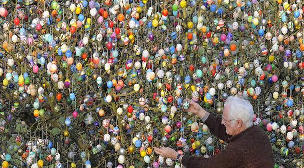 German Volker Kraft and his garden tree that he decorated with 10,000 Easter eggs (AP)
