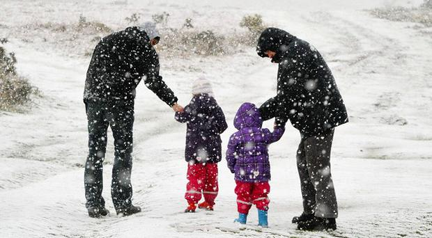 A family walk in the snow in the Brecon Beacons, south Wales, as freezing gales and snow brought Britain's early summer to an abrupt end