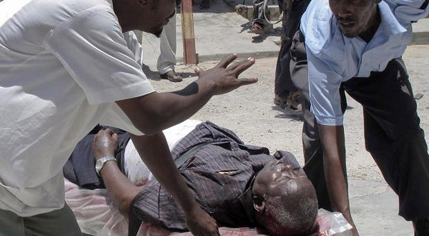 A man wounded in a deadly blast at the Somali National Theatre in Mogadishu is stretchered away