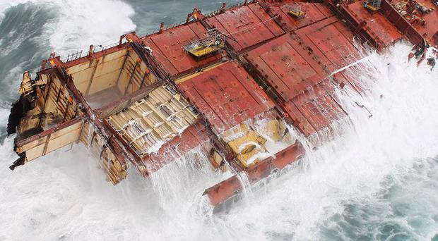 The broken hull of the Rena can be seen in heavy sea swells on a reef near Tauranga, New Zealand (AP/Maritime NZ)
