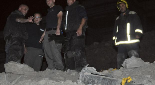 Police and firefighters at the scene where the rocket landed in Eilat, southern Israel (AP)