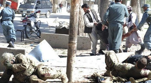 Wounded US soldiers lie on the ground at the scene of a Taliban suicide attack at a park in northern Afghanistan (AP)