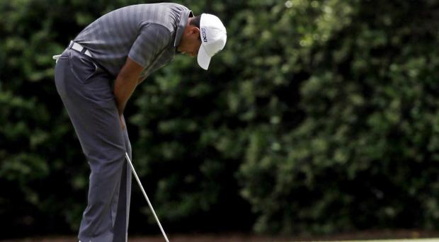 Tiger Woods reacts after missing a birdie putt on the 11th green during the first round the Masters golf tournament Thursday, April 5, 2012, in Augusta, Ga
