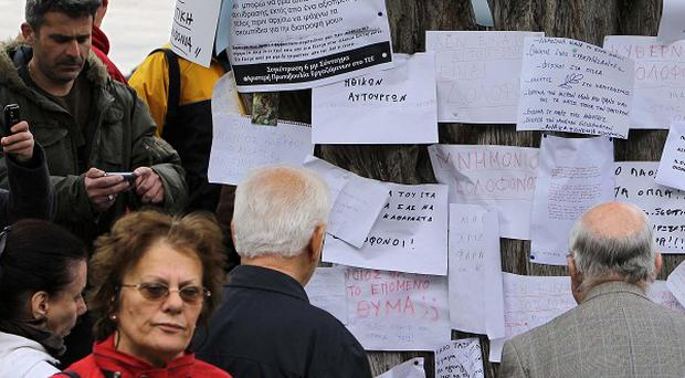 People read tributes left at the site where an elderly man fatally shot himself in Athens (AP)