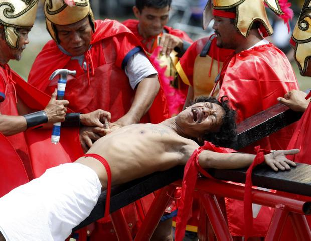 Volunteers dressed as Roman Centurions, drive nails through the palms of an unidentified Catholic devotee in a reenactment of the crucifixion of Jesus Christ on Good Friday at San Pedro Cutud, Pampanga province, north of Manila, Philippines