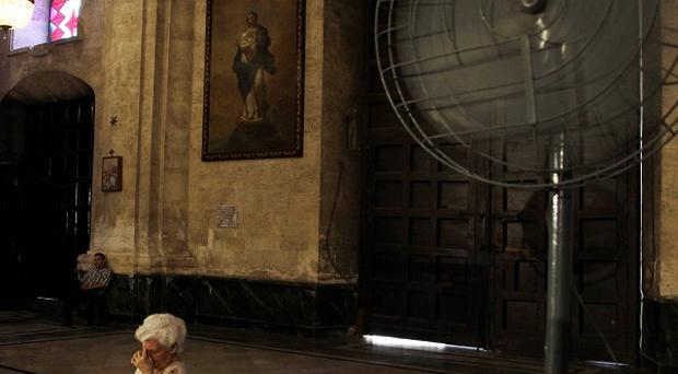 A woman prays at Good Friday Mass during Holy Week in the cathedral in Havana, Cuba (AP)