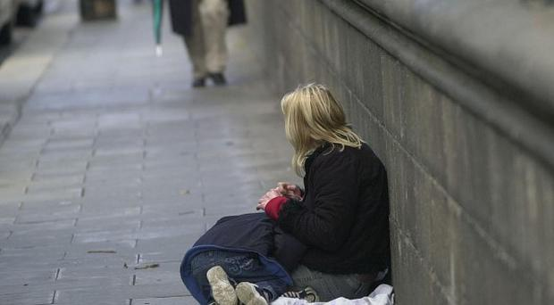 A woman begs with a child on the streets of Dublin on the day that Combat Poverty released their annual report, in Dublin, Ireland. Nearly a quarter of Irish children are living in low income households, new figures revealed today. The number of youngsters whose families were below the income poverty line of 104 (147 euros) per week has increased sharply since 1994, when the figure stood at 15%. Single-parent families and households with four or more children were most likely to be living in poverty.