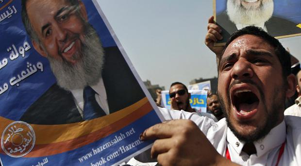 Egyptian protesters chant slogans holding posters of under fire presidential candidate, Hazem Abu Ismail (AP)