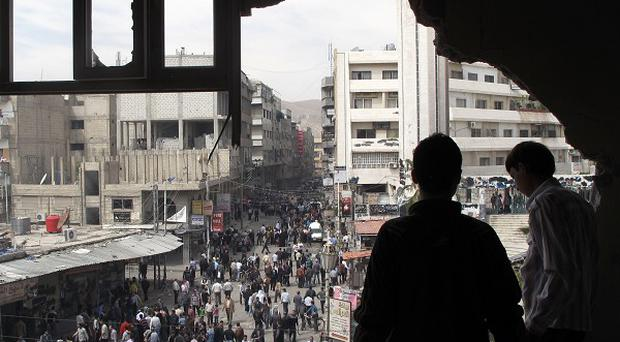 Youths look out of a building damaged by tank shells in Damascus, Syria (AP)