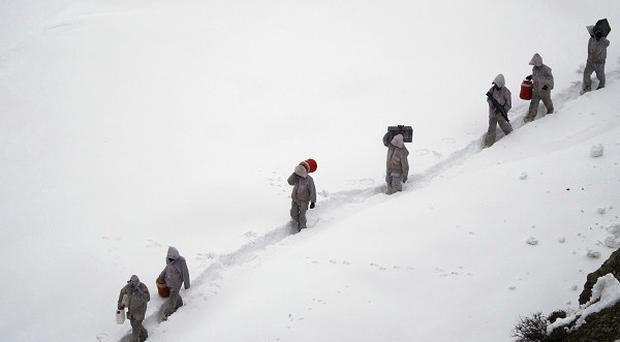 Pakistani Army soldiers carry supplies near their outpost, Kalpani Base, in Dir district (AP)