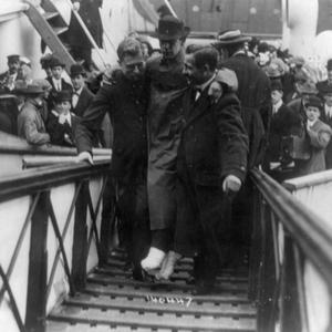 In this 1912 photo made available by the Library of Congress, Harold Bride, surviving wireless operator of the Titanic, with feet bandaged, is carried up the ramp of a ship.