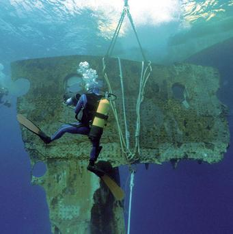 A diver accompanies a 17-ton portion of the hull of the Titanic as it is lifted to the surface in the Atlantic Ocean.