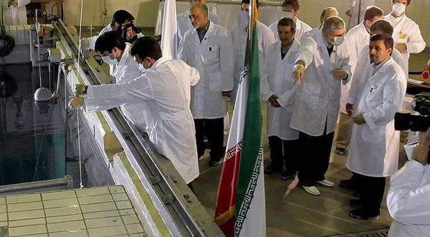 Iranian President Mahmoud Ahmadinejad, right, during a tour of Tehran's research reactor centre in northern Tehran (AP)