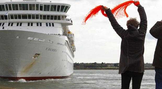 People wave at the Balmoral cruise ship as it leaves Southampton docks on the official Titanic centenary voyage