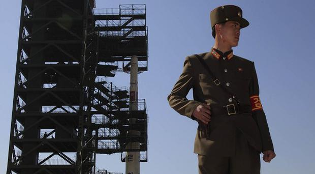 A North Korean soldier stands in front of the country's Unha-3 rocket at Sohae Satellite Station in Tongchang-ri (AP)