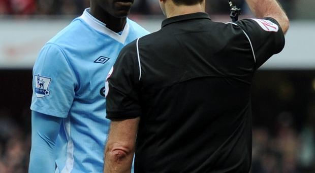 LONDON, ENGLAND - APRIL 08: Referee Martin Atkinson shows Mario Balotelli of Man City a red card during the Barclays Premier League match between Arsenal and Manchester City at Emirates Stadium on April 8, 2012 in London, England. (Photo by Michael Regan/Getty Images)