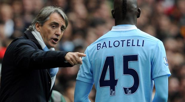 LONDON, ENGLAND - APRIL 08: Man City manager Roberto Mancini has words Mario Balotelli of Man City during the Barclays Premier League match between Arsenal and Manchester City at Emirates Stadium on April 8, 2012 in London, England. (Photo by Michael Regan/Getty Images)