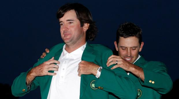 AUGUSTA, GA - APRIL 08: Bubba Watson of the United States (L) is awarded the green jacket by Charl Schwartzel of South Africa (R) during the green jacket presentation after his one-stroke playoff victory during the 2012 Masters Tournament at Augusta National Golf Club on April 8, 2012 in Augusta, Georgia. (Photo by Streeter Lecka/Getty Images)