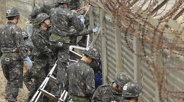 South Korean soldiers remove a barbed wire fence erected four decades ago to prevent North Korean infiltrators entering the south (AP)
