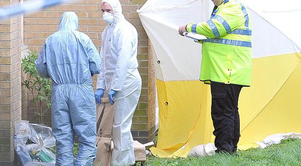 Police and forensics officers attend the scene after an 18-year-old woman fell to her death from a block of flats in Woolwich