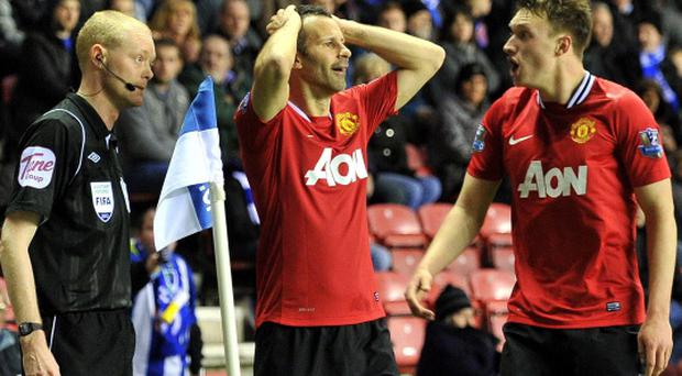 Manchester United's Ryan Giggs and Phil Jones (right) appeal to the linesman for a handball in the penalty area during the Barclays Premier League match at the DW Stadium, Wigan