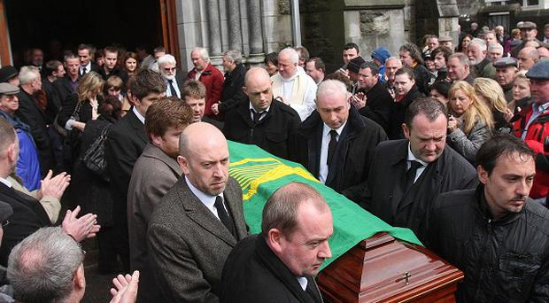 Mourners applaud as the coffin of Dubliners' musician Barney McKenna leaves St Patrick's Church in Trim, Co Meath