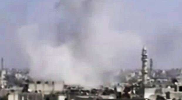 Smoke rises following alleged shelling in Homs, Syria (AP/Syrian Media Council via AP video)