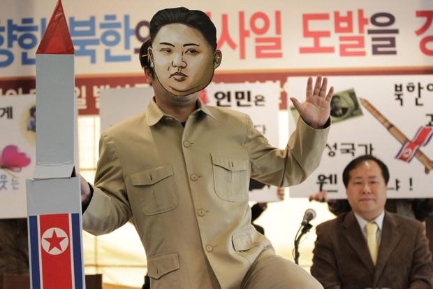 A South Korean activist wearing a mask of North Korean leader Kim Jong Un holds a mock rocket during a protest event against North Korea's rocket launch in Seoul, South Korea, Friday, April 13, 2012
