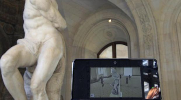 A visitor studies a Michelangelo sculpture in the Louvre with the help of the new audio guide (AP/Jacques Brinon)