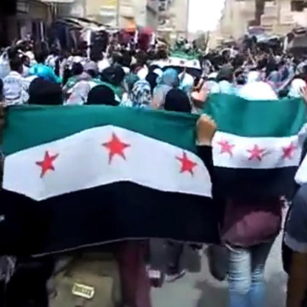 Protesters hold Syrian revolutionary flags during a demonstration in Deir el-Zour, Syria (AP)