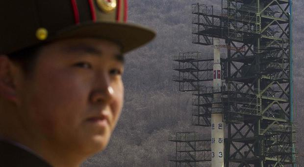 A North Korean soldier stands in front of the country's Unha-3 rocket at a launching site in Tongchang-ri (AP)