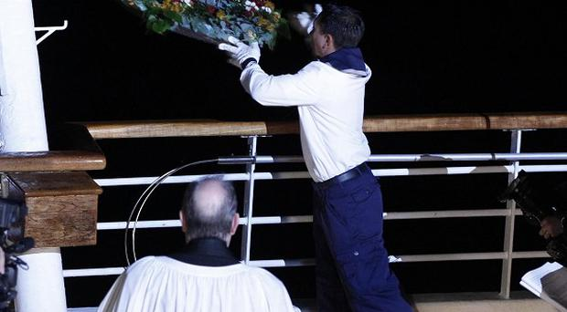 A crew member throws a wreath overboard during a memorial service, marking the 100th year anniversary of the Titanic disaster (AP)