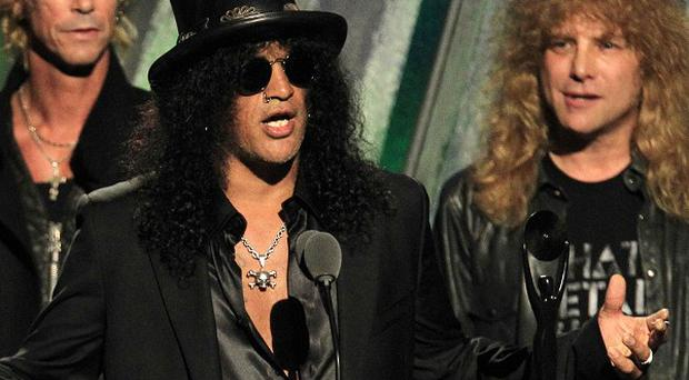 Slash with Duff McKagan, left, and Steven Adler after Guns N' Roses was inducted into the Rock and Roll Hall of Fame (AP/Tony Dejak)