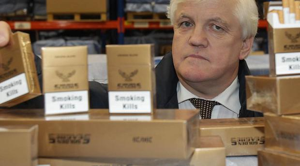Customs officer Mick Hannon with some of the 38 million contraband cigarettes seized at Dublin Port