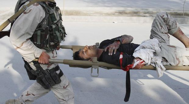 Afghan special forces carry a wounded colleague after gun battles in Kabul (AP)