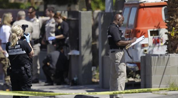 Crime scene investigators at a house where two bodies and an injured man were found (AP)