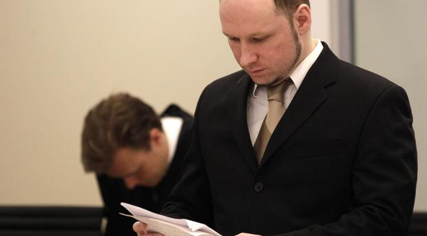 Accused Norwegian Anders Behring Breivik looks at papers at the courtroom, in Oslo, Norway, Tuesday April 17, 2012. The anti-Muslim fanatic who admitted to killing 77 people in a bomb-and-shooting massacre took to the stand in his terror trial today
