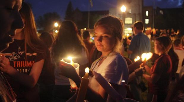 Virginia Tech students pass the flame of a memorial candle during a vigil on the Blacksburg campus (AP)