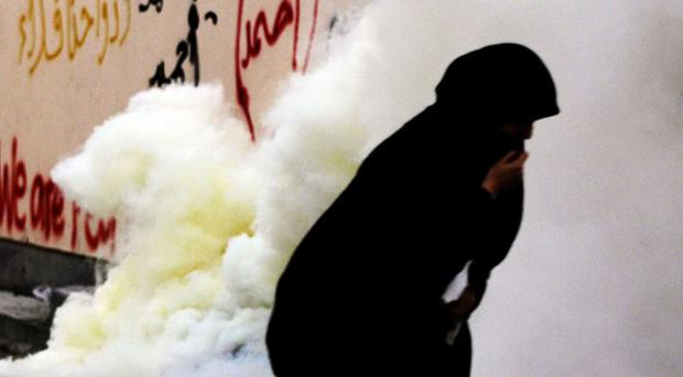 A Bahraini woman reacts to tear gas fired by riot police during clashes (AP)