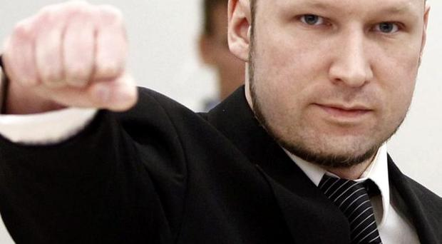 Anders Behring Breivik gestures on arrival at the courtroom, in Oslo, Norway, Wednesday April 18, 2012.